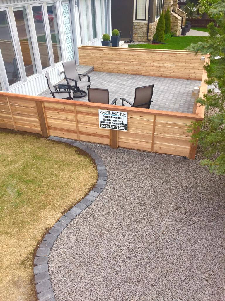 Fences - decorative horizontal slat cedar fence around a front yard patio.