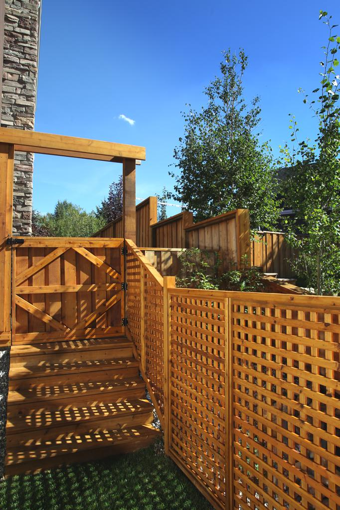 Fences - stained cedar lattice fence with half gate and arbor
