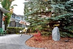 Paving stone patio with cedar mulch and a decorative address boulder