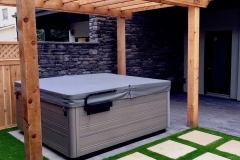 cozy hot tub area with paving stone stepping stones and artificial turf