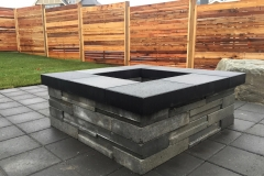 horizontal style fence with stone fire pit on a paving stone patio